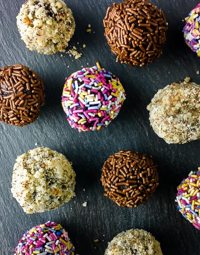 Healthy raw vegan chocolate truffles rolled in a selection of ground nuts and sprinkles, on a dark slate surface.