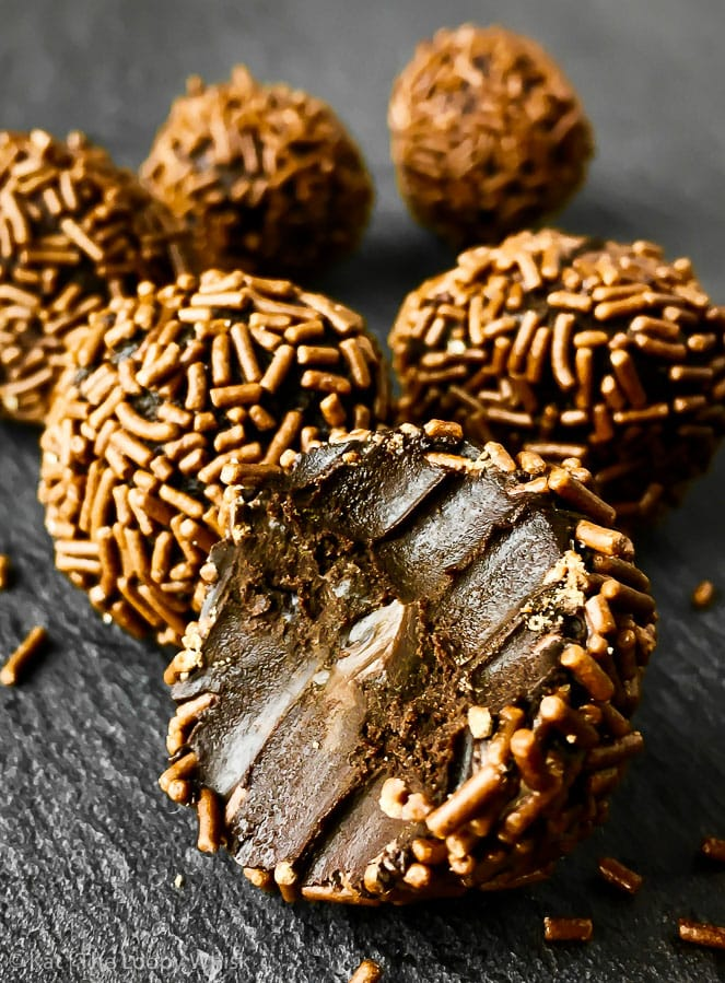 Close-up of a dark chocolate raw vegan chocolate truffle, rolled in dark chocolate sprinkles.