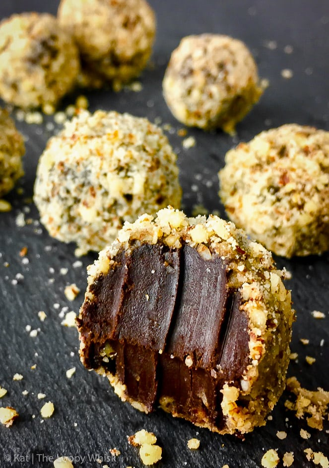 Close-up of a dark chocolate raw vegan chocolate truffle, rolled in ground hazelnuts.
