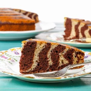 Gluten Free Zebra Cake - This fun and delicious gluten free zebra cake is super easy to make and bound to impress just about anyone. Chocolate and vanilla batters complement each other perfectly in this sweet, moist and airy cake that is suitable for all occasions, from posh afternoon tea to a children's party, on its own or frosted in buttercream, dusted with icing sugar, or smothered in chocolate ganache.