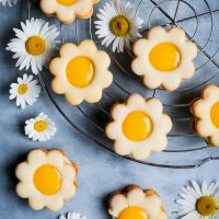 Daisy Lemon Curd Sandwich Cookies {gluten, nut & soy free} - These lemon curd cookies are every lemon dessert lover's dream. Delicious homemade lemon curd and creamy buttercream are sandwiched between gluten free lemon cookies covered with lemon icing – and to top it all off, these daisy sandwich cookies couldn't be prettier if they tried!