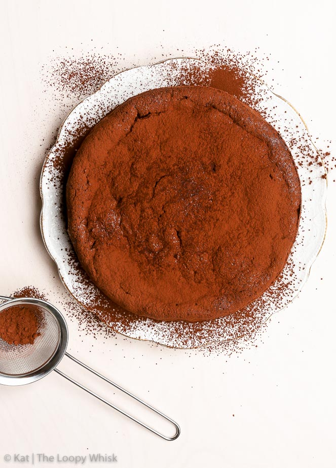 An easy and healthy flourless chocolate cake, dusted with cocoa powder.
