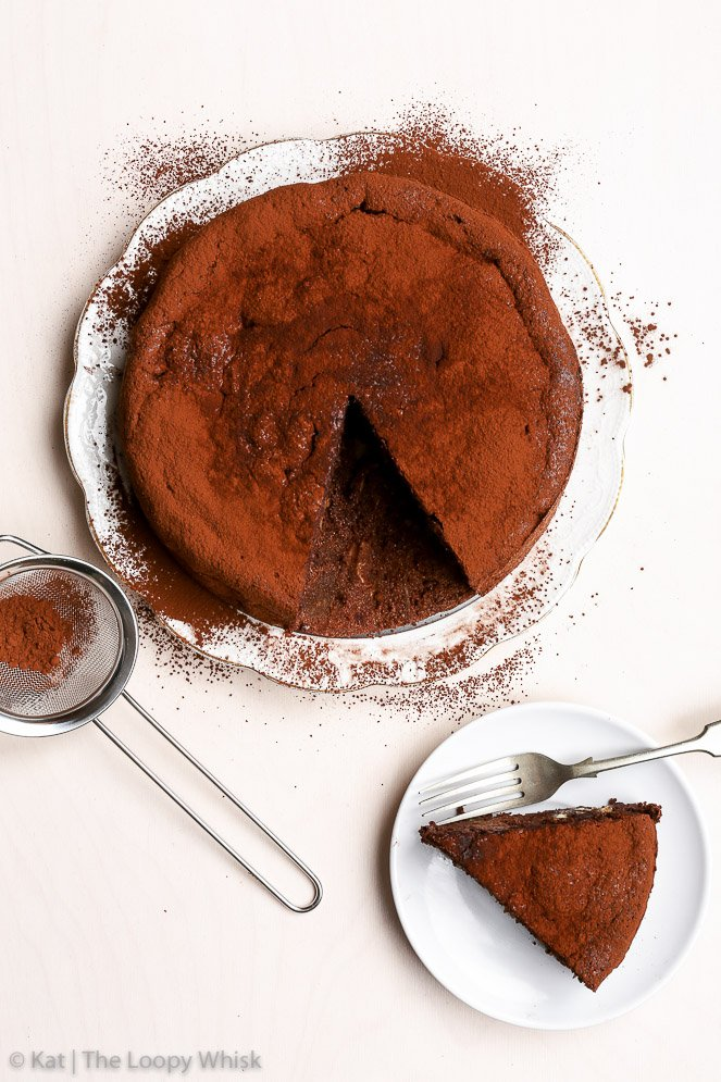 An easy and healthy flourless chocolate cake, dusted with cocoa powder. A single slice of the cake cut out and placed onto a plate.