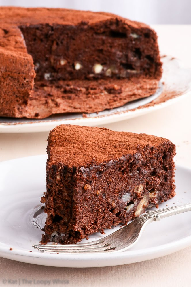 A slice of the easy healthy flourless chocolate cake, with the whole cake in the background.