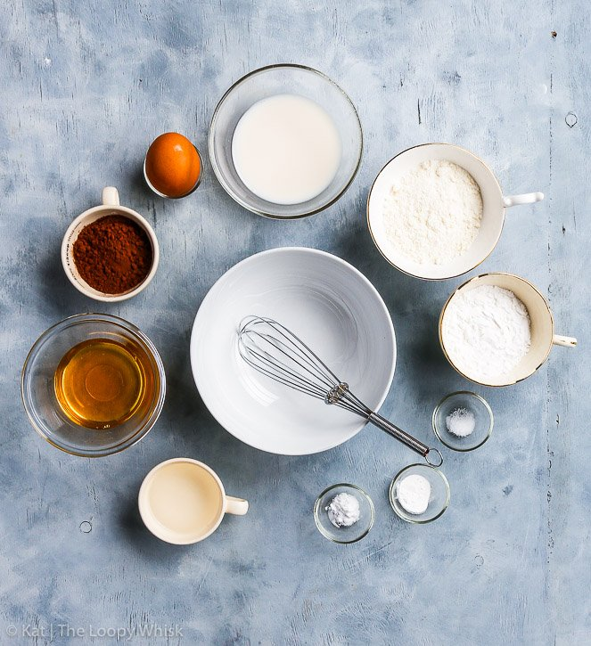 The healthy paleo chocolate cake ingredients set out in a circle on a grey-blue background. Bird's eye view. Clockwise: melted coconut oil, honey, cocoa powder, eggs, almond milk, coconut flour, arrowroot flour, salt, baking soda and baking powder. An empty bowl with a whisk is in the middle.