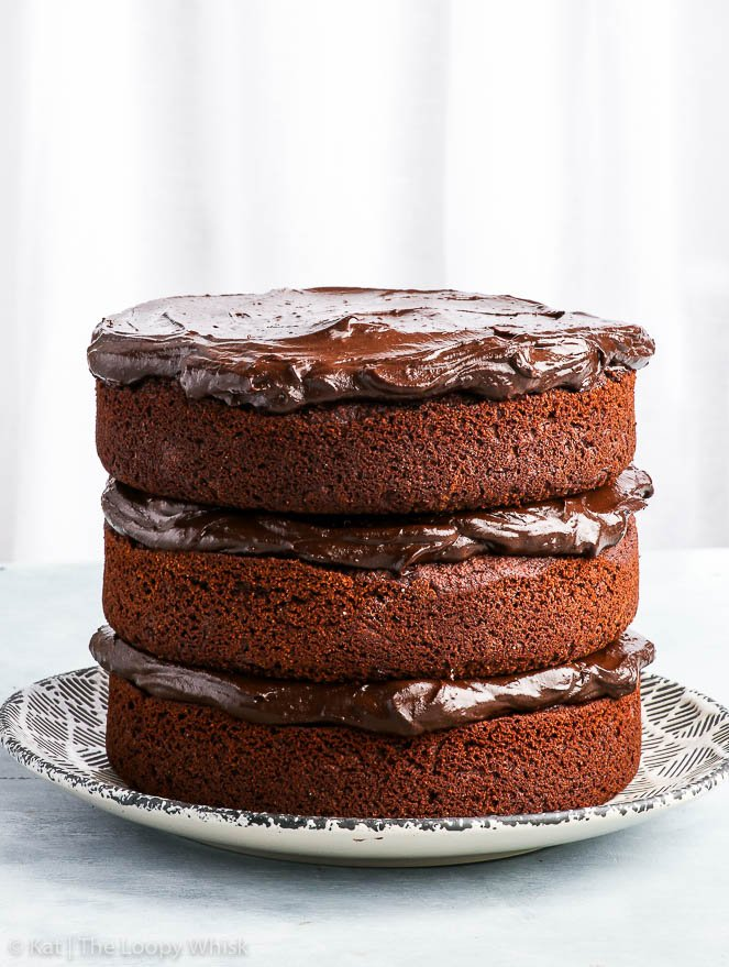 The healthy paleo chocolate cake sits on a decorative black and white plate, in a bright setting.