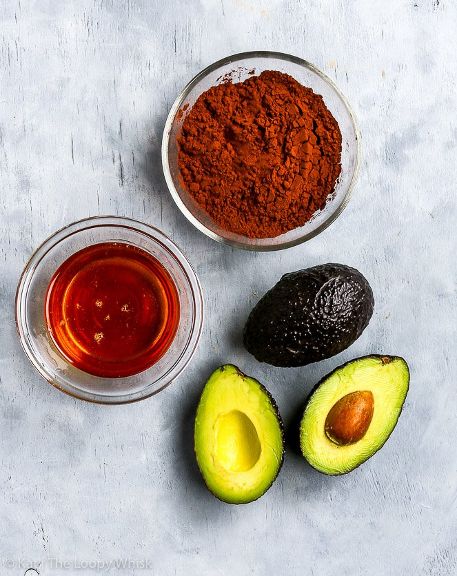 The three ingredients of the healthy paleo & vegan chocollate frosting: ripe avocados, cocoa powder and honey or maple syrup.