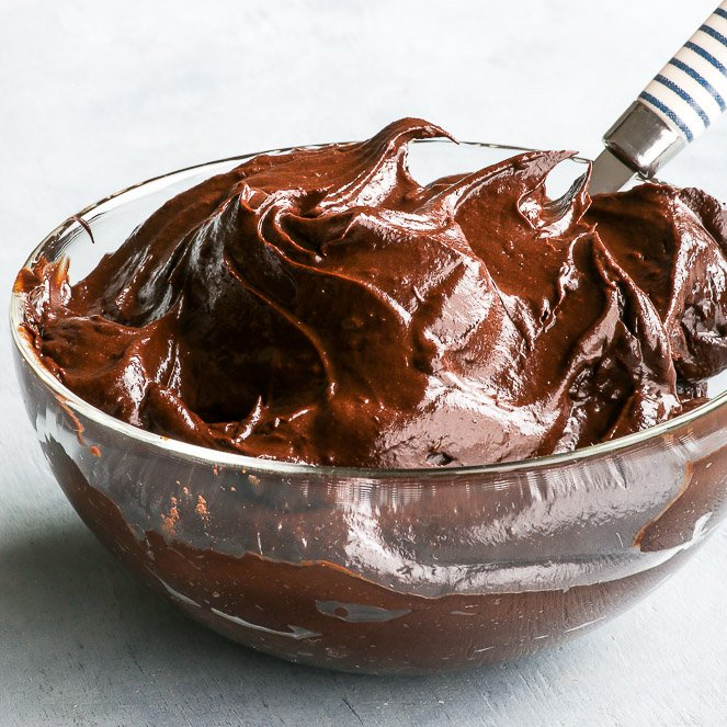 A bowl full of delicious, luscious paleo avocado ganache, with a white and blue striped spoon in the bowl.