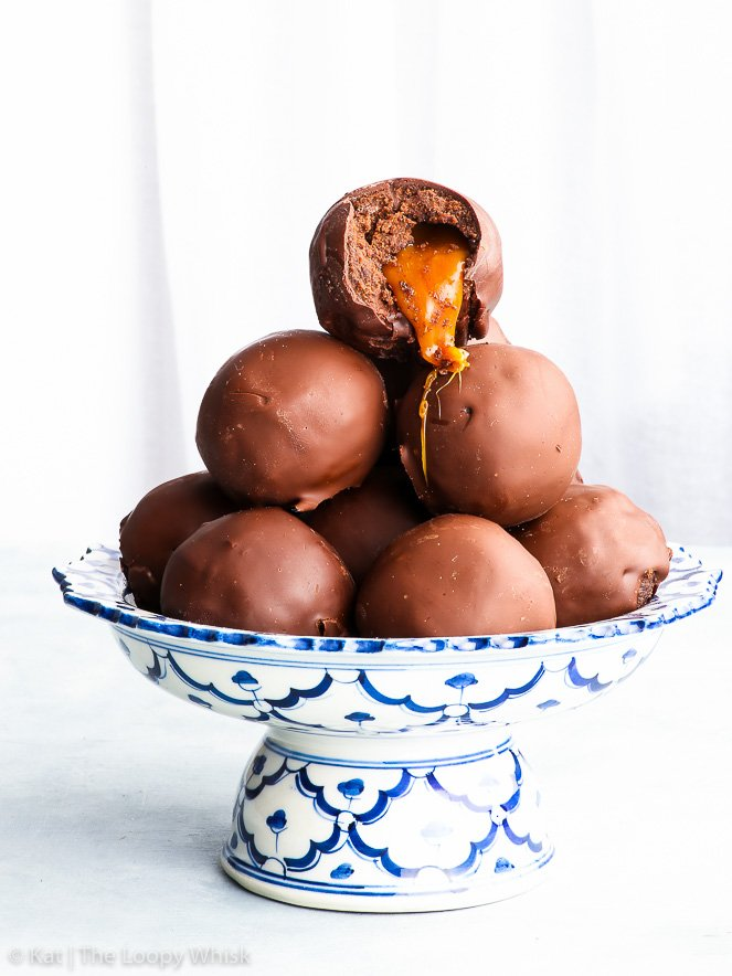 Salted caramel brownie truffles heaped on a pretty antique white and blue stand. A bite has been taken out of the top brownie truffle and the salted caramel is oozing out of the centre, looking absolutely mouth-watering.