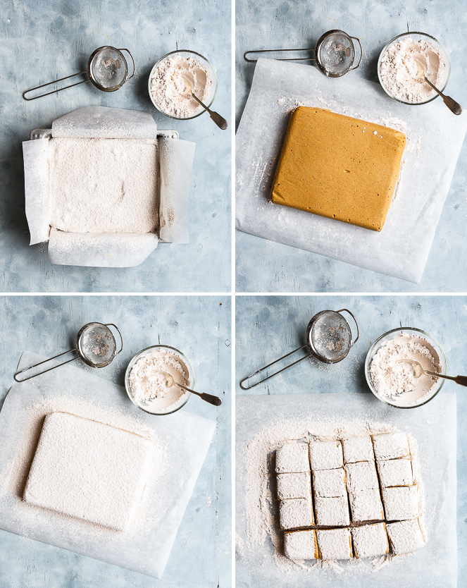 The process of coating and cutting the homemade gingerbread marshmallows, in bird's eye view. Top left: The marshmallow mixture is still in the baking pan. The top has been generously sprinkled with the powdered sugar mixture. Top right: The marshmallow block has been turned onto a sheet of parchment paper, leaving its golden brown bottom side exposed. Bottom left: The other side of the marshmallow block is generously coated with the powdered sugar mixture. Bottom right: The coated marshmallow block is cut into even pieces.