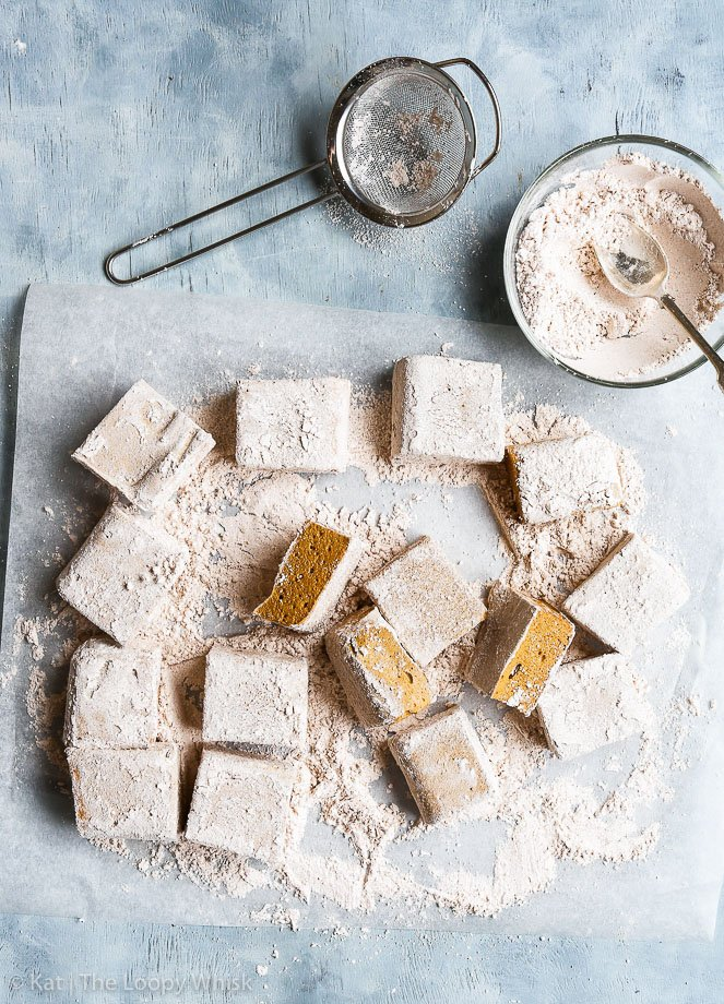 Bird's-eye view of the cut homemade gingerbread marshmallows, which have been rolled in the spiced powdered sugar mixture.