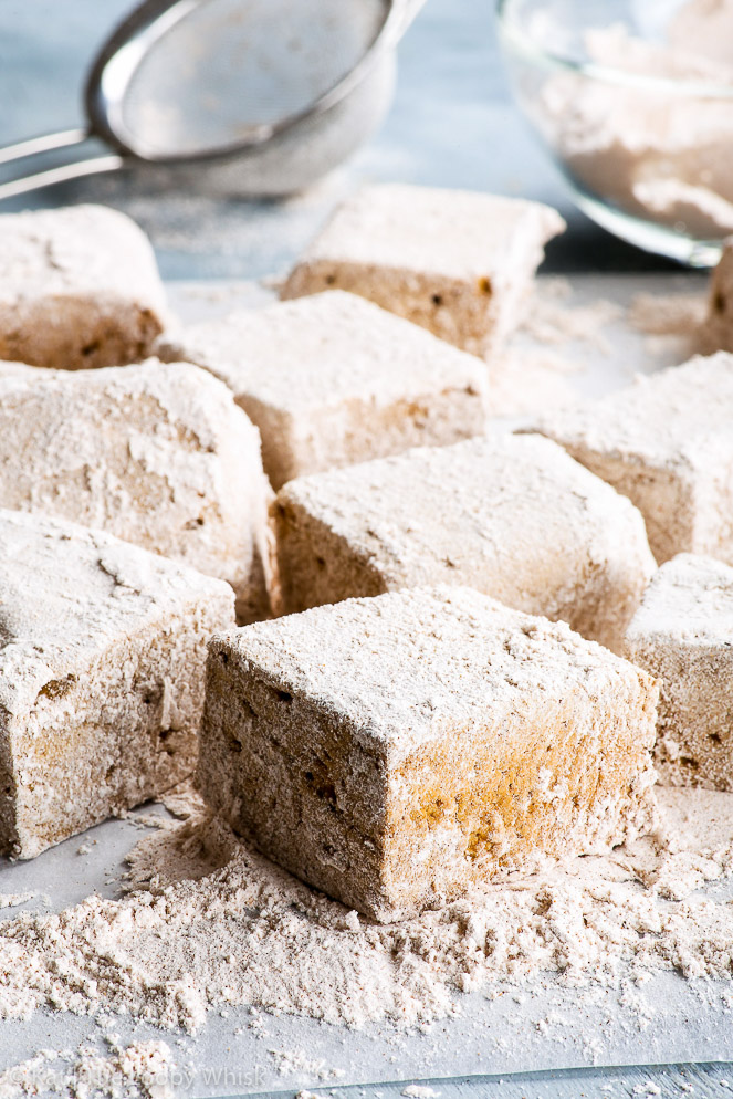 Homemade gingerbread marshmallows on a blueish grey surface, sprinkles with plenty of the spiced powdered sugar mixture. A sieve and a glass bowl containing the powdered sugar are in the background.