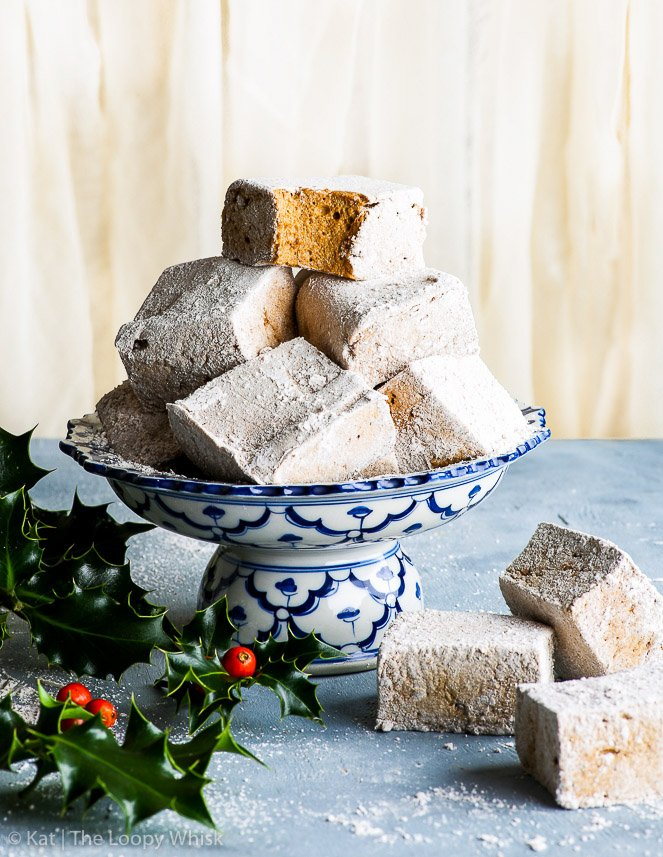 A pretty heap of homemade gingerbread marshmallow sits on top of a decorative blue and white antique stand. A bite has been taken out of the top marshmallow, exposing its golden brown fluffy middle. A few marshmallow pieces and a bunch of holly surrounds the stand.
