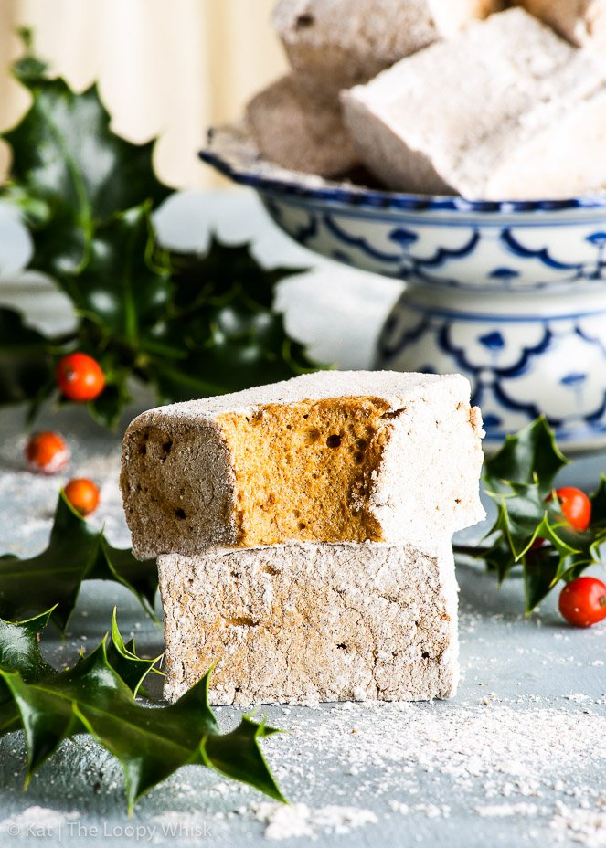 Two pieced of homemade gingerbread marshmallows, one on top of the other. A bit has been taken out of the top gingerbread marshmallow, exposing its golden brown, fluffy middle. Bunches of holly and a pretty white and blue antique stand are in the background.