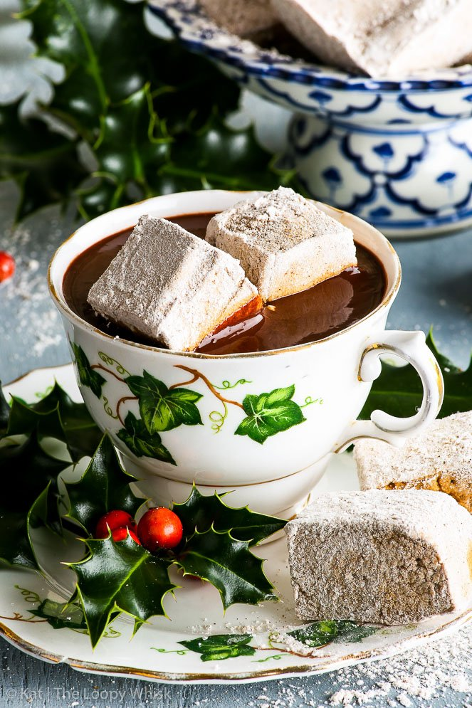 A decorative antique cup and saucer, both with green ivy decorations. The cup is full of luscious homemade hot chocolate. Two pieces of the gingerbread marshmallows are in the hot chocolate, partially melted.