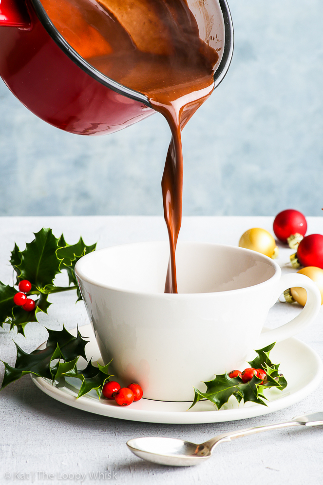 Luscious, decadent homemade hot chocolate being poured into a white cup from a red saucepan. Bunches of holly and Christmas baubles give a Christmas atmosphere to the photo.