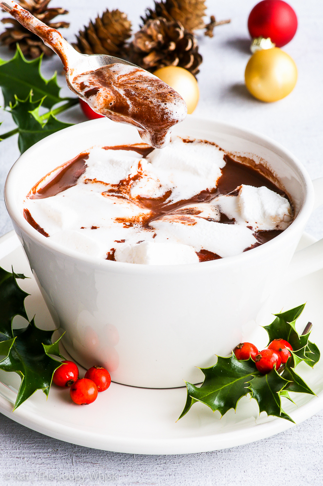 Homemade hot chocolate in a white cup with homemade marshmallows floating on top. Bunches of holly and Christmas baubles give a Christmas atmosphere to the photo.