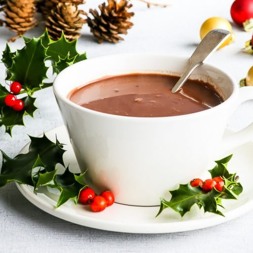 Homemade hot chocolate in a white cup, with holly leaves and berries around the cup. Some pinecones and Christmas baubles in the background.