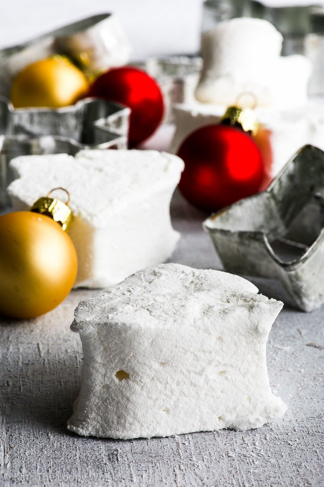 White, fluffy marshmallow is in the front, with more marshmallows and cookie cutters in the background. Red and gold Christmas baubles in the background give a pop of colour.