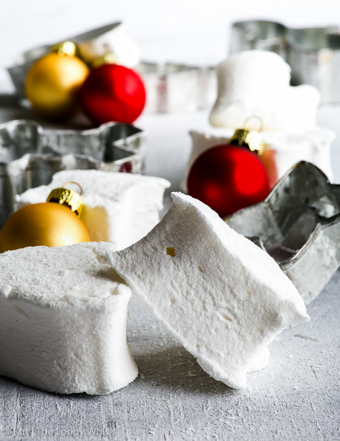 Two white, fluffy marshmallows, partially stacked on top of each other are in the front, with more marshmallows and cookie cutters in the background. Red and gold Christmas baubles in the background give a pop of colour.
