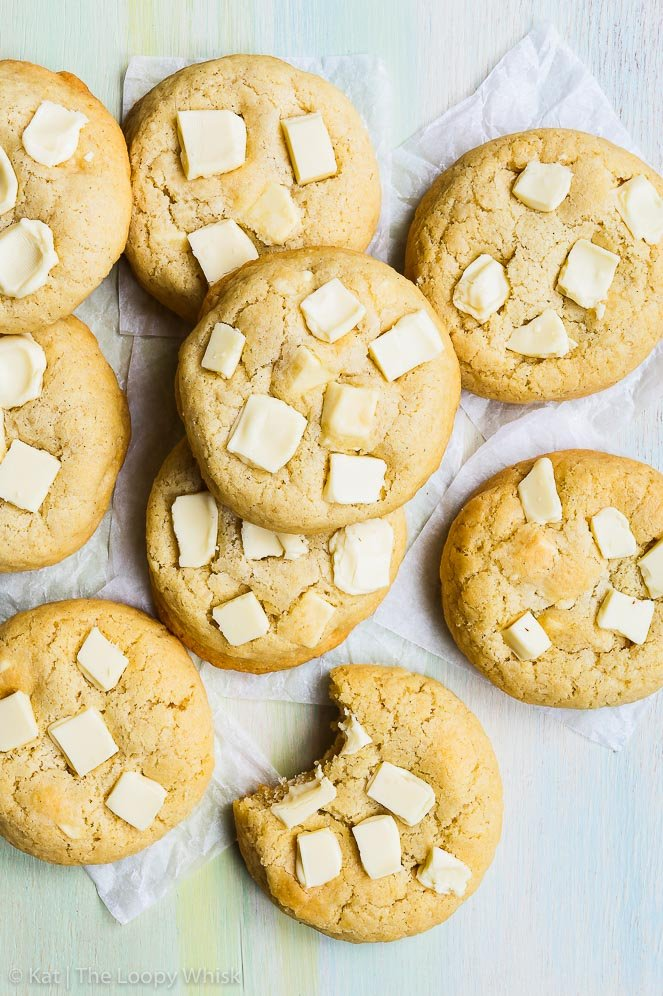 Bird's-eye view of gluten free white chocolate chip cookies, arranged in a small pile on a greenish surface with some white parchment paper underneath. One of the cookies has had a bite taken out of it.