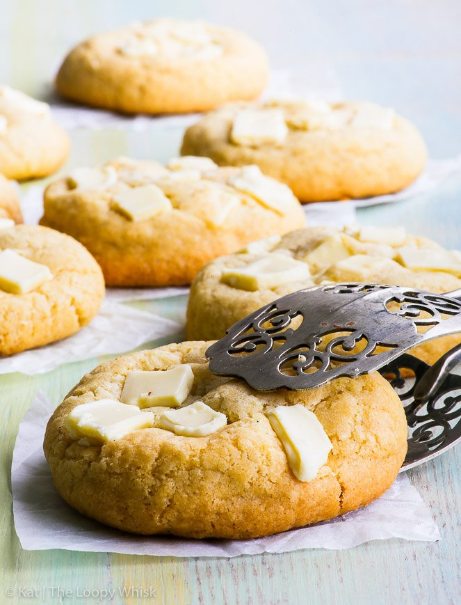 A side view of a gluten free chocolate chip cookie, being held with decorative tongs. More white chocolate chip cookies are in the background.