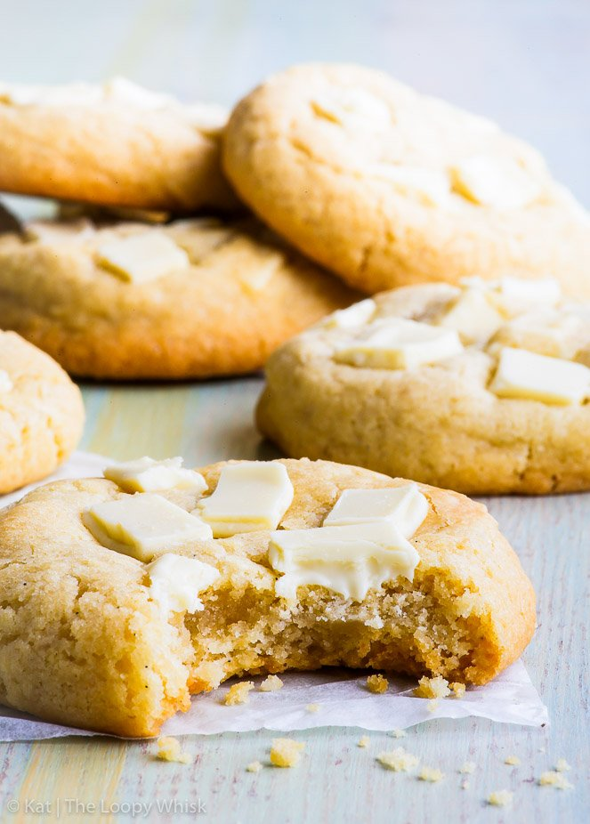 Side view of a chewy, buttery gluten free white chocolate chip cookie that has had a bite taken out of it. More white chocolate chip cookies are in the background.