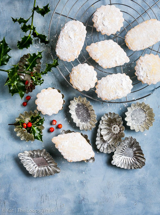 Bird's-eye view of gluten free Croatian bear paw cookies on a greyish blue background. Some of the cookies are on a cooling rack. The fluted cookie molds lie in between the cookies, and bunches of holly give a Christmassy atmosphere.