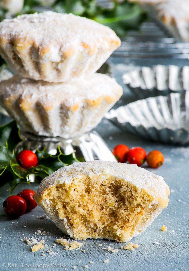 A stack of two gluten free Croatian bear paw cookies, standing on a fluted cookie mould. Next to them, a cookie has a bite taken out of it, exposing its buttery, slightly crumbly texture. Bunches of holly add to the festive holiday atmosphere.