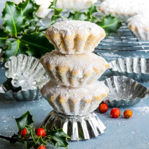 A stack of three gluten free Croatian bear paw cookies, standing on a fluted cookie mould. Bunches of holly add to the festive holiday atmosphere.