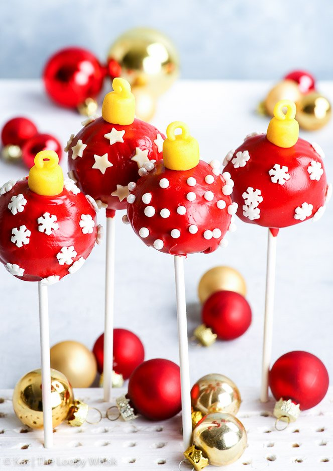 Gluten free Christmas bauble cake pops arranged in a white stand on a white surface and in front of a light blue background. Red and gold Christmas baubles add to the holiday mood.