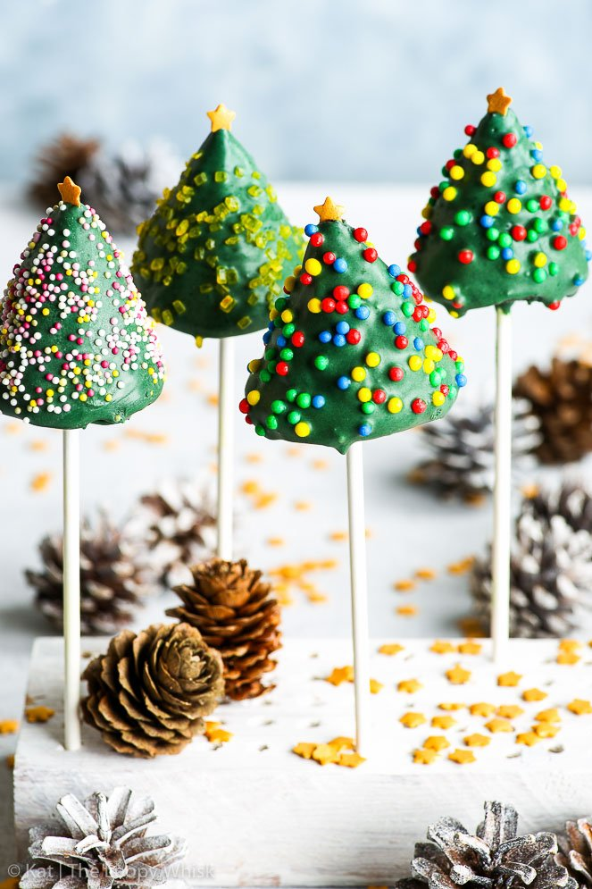 Gluten free Christmas tree cake pops arranged in a white stand on a white surface and in front of a light blue background. Gold star sprinkles and white sprayed pinecones add to the holiday mood.