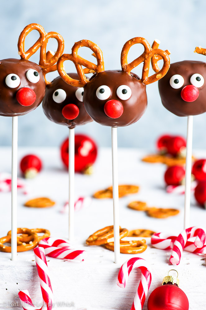 Gluten free Rudolph the red nosed reindeer cake pops arranged in a white stand on a white surface and in front of a light blue background. Small candy canes and Christmas baubles add to the holiday mood.