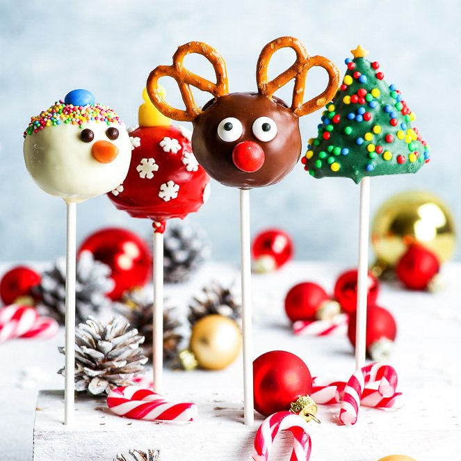 Gluten free Christmas cake pops arranged in a white stand on a white surface and in front of a light blue background. From left to right: snowman cake pop, Christmas bauble cake pop, Rudolph reindeer cake pop, Christmas tree cake pop. Small candy canes, white sprayed pinecones and Christmas baubles add to the holiday mood.