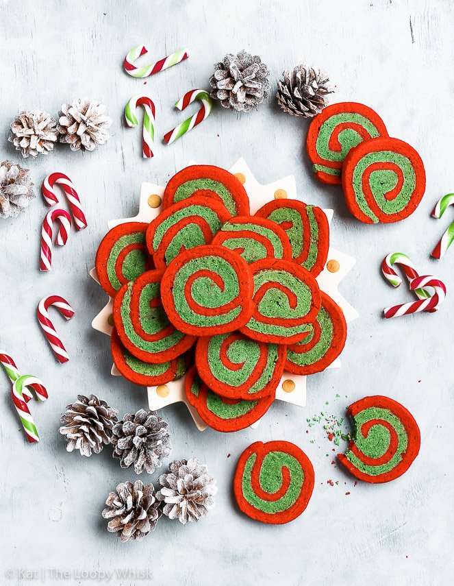 A bird's eye view of the gluten free red and green Christmas pinwheel cookies on a pale greyish blue background. White sprayed pinecones and small candy canes add to the Christmas atmosphere.
