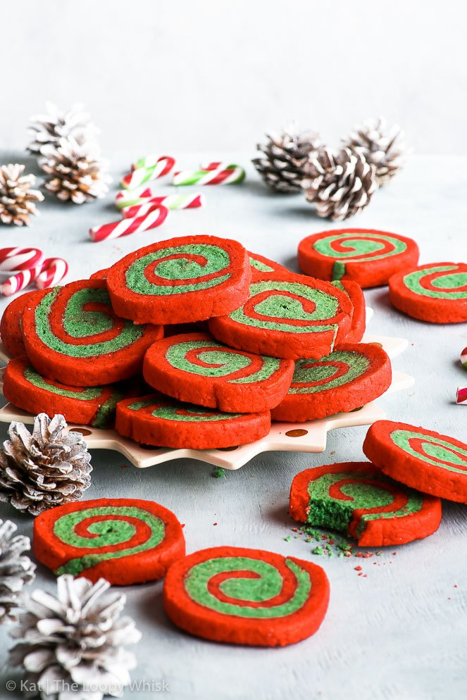 Side view of the gluten free red and green Christmas pinwheel cookies arranged on a decorative star-shaped plate, on a pale greyish blue background. White sprayed pinecones and small candy canes add to the Christmas atmosphere.