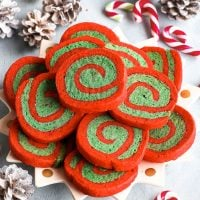 A bird's eye view of the gluten free red and green Christmas pinwheel cookies arranged on a decorative star-shaped plate, on a pale greyish blue background. White sprayed pinecones and small candy canes add to the Christmas atmosphere.