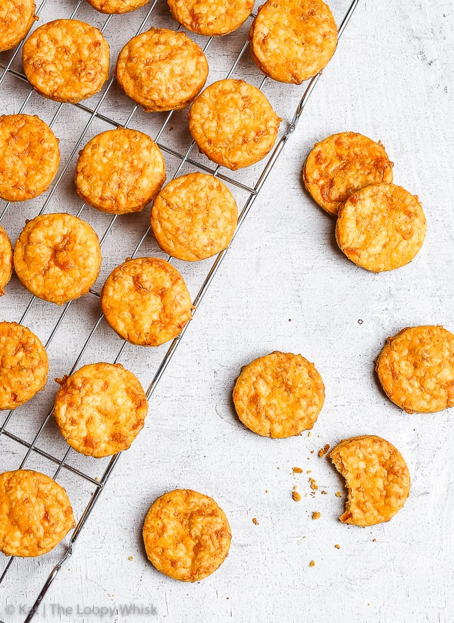 Bird's-eye view of the spicy cheddar gluten free crackers on a white background. Most of the golden brown cheddar crackers, with a slight orangish tinge, are on a metal cooling rack. A few are off the cooling rack, one has had a bite taken out of it.