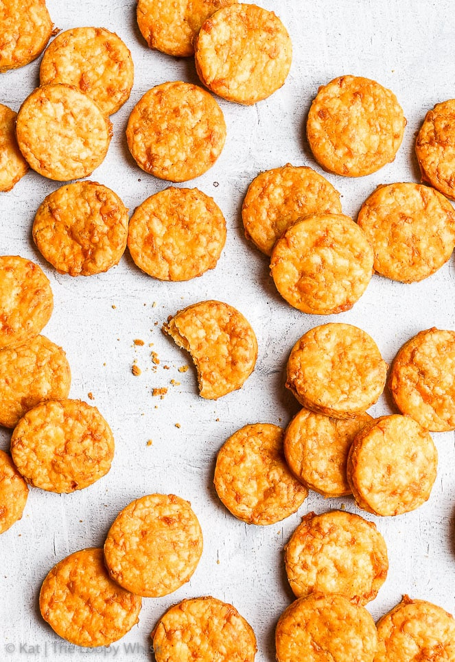 Bird's-eye view of the spicy cheddar gluten free crackers on a white background. The golden cheddar crackers have a light orangish tinge to them. They are piled haphazardly one on top of the other, one has had a bite taken out of it.