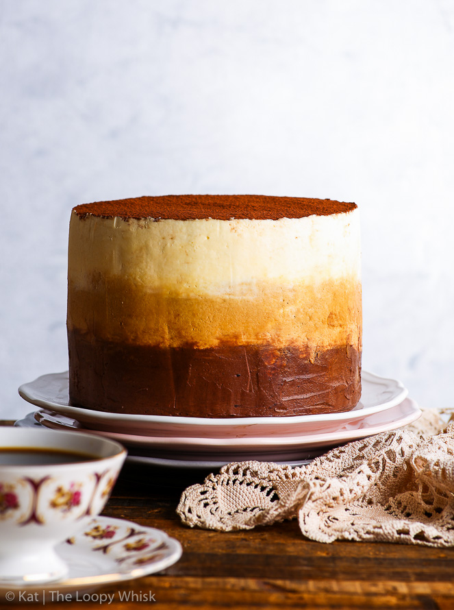 The gluten free tiramisu cake is placed on a white plate, which sits on top of two more decorative plates - a pink and a grey one. A pretty lace napkin is on the right side next to it, and a antique coffee cup and sauces are in the foreground.