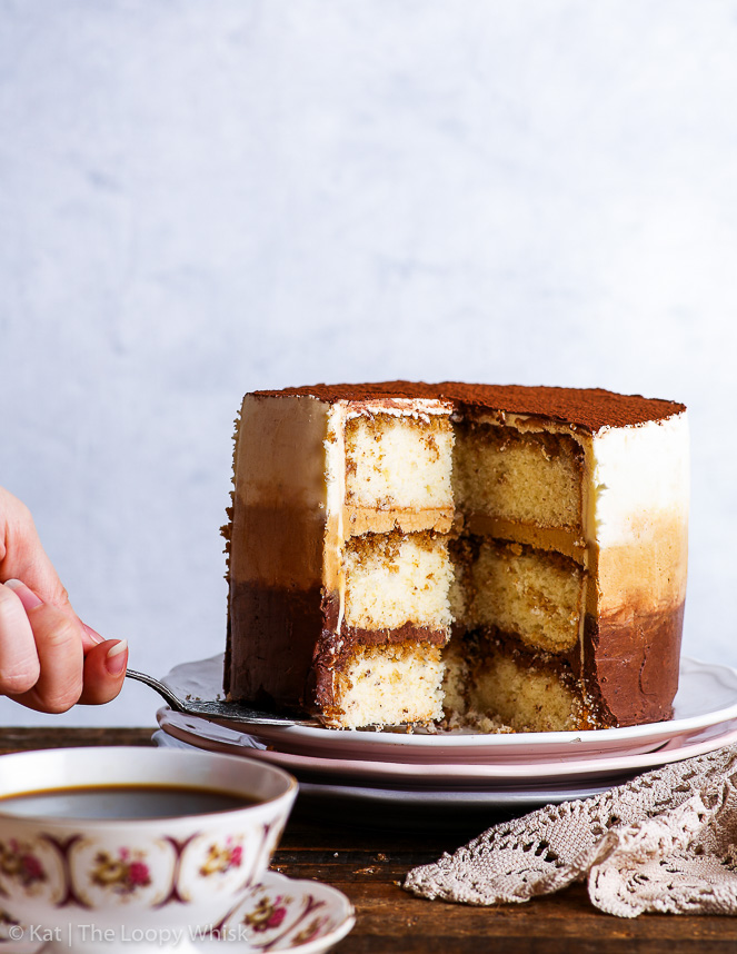 The gluten free tiramisu cake is placed on a white plate, which sits on top of two more decorative plates - a pink and a grey one. A slice has been cut and is the process of being removed with a pretty antique cake server. A pretty lace napkin is on the right side next to it, and a antique coffee cup and sauces are in the foreground.