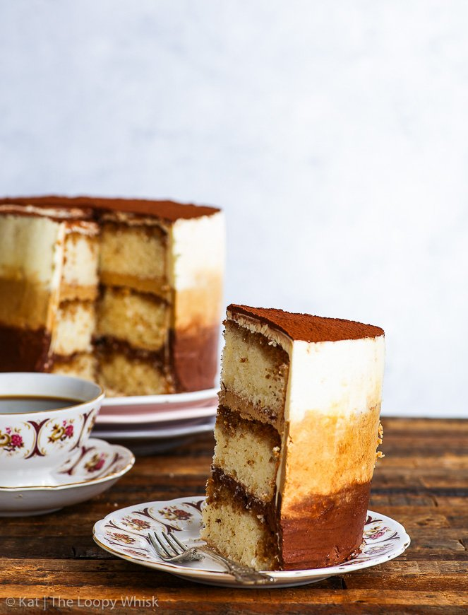 A slice of the gluten free tiramisu cake is on a decorative plate in the foreground. It is turned with its back to the front, emphasising the ombre frosting, achieved with the chocolate, coffee and plain mascarpone buttercream. The rest of the gluten free tiramisu ombre cake is in the background.