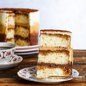 A slice of the gluten free tiramisu cake is on a decorative plate in the foreground. The layers of fluffy genoise, soaked in coffee, as well as chocolate, coffee and plain mascarpone buttercream are nicely distinguishable. The rest of the gluten free tiramisu ombre cake is in the background.