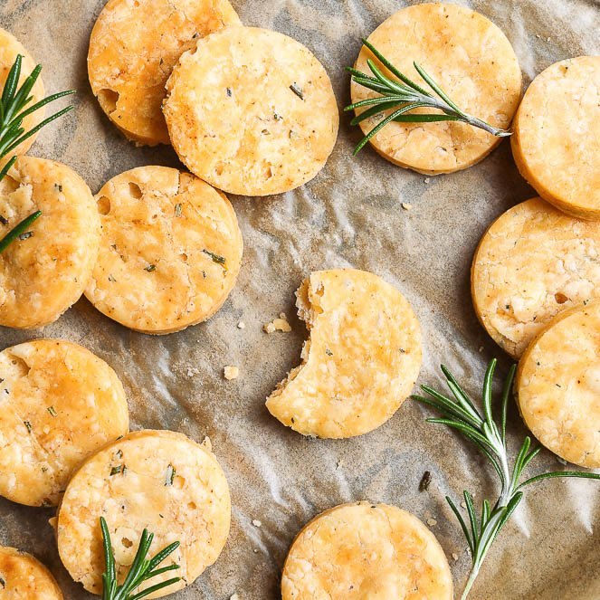 Bird's-eye view of gluten free vegan crackers with rosemary on a baking tray lines with baking paper. Rosemary sprigs are sprinkled among the flaky, buttery vegan crackers.