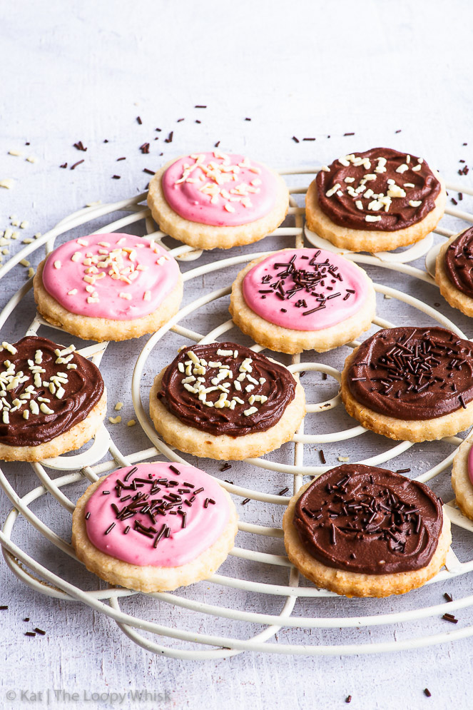 Pretty frosted gluten free vegan sugar cookies arranged on a decorative white cake cooling rack. The gluten free sugar cookies have been frosted with two types of easy vegan frosting (brown and pink) and decorated with white and dark chocolate sprinkles.