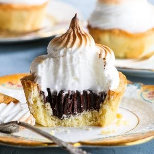 A hot chocolate cookie cup on a decorative antique plate. A piece has been taken with a fork, exposing the crumbly cookie cup texture, the luscious dark chocolate ganache centre and the fluffy marshmallow-like swiss meringue frosting. Two more gluten free cookie cups are in the background.