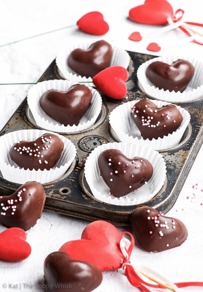 Raspberry mousse heart chocolates arranged in small cupcake paper cases, in an old slightly rusted cupcake tin. Red heart-shaped decorations are arranged on and around the cupcake tin, creating a romantic Valentine's Day atmosphere.