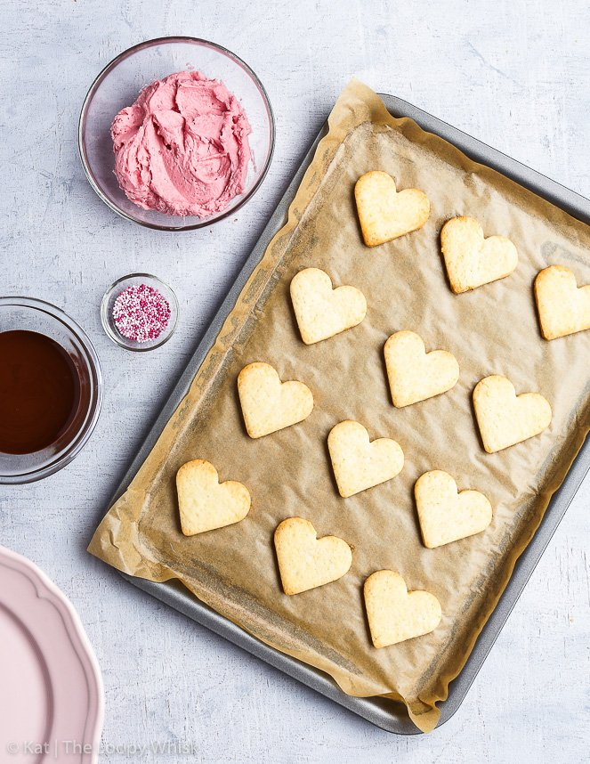 Bird's-eye view of the process of making Valentine's gluten free heart cookies: the heart-shaped cookies are on a baking sheet, next to it are three small glass bowls, filled with raspberry frosting, melted chocolate and sprinkles.