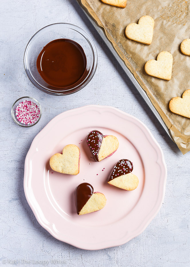 Four Valentine's heart cookies arranged on a decorative pink plate. One is plain, one dipped into chocolate and two both dipped into chocolate and decorated with sprinkles. The glass bowls containing melted chocolate and sprinkles are next to the plate. In the top right corner, there is a baking sheet with the gluten free cookies.