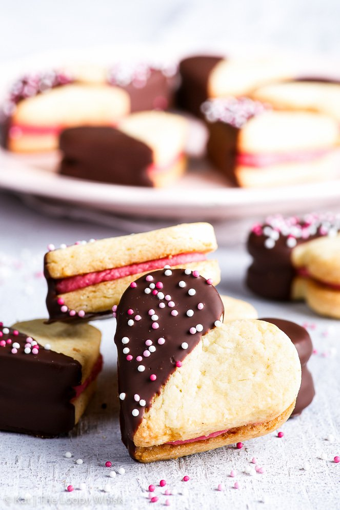 A Valentine's heart cookie is in the foreground – heart-shaped cookie sandwich, dipped into chocolate and decorated with pretty sprinkles. More gluten free heart cookies are in the background. A pretty pink plate is also in the background.
